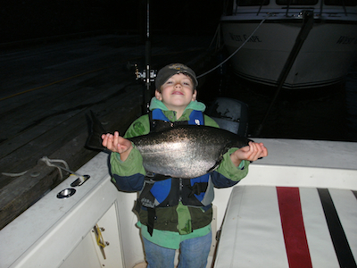 young boy holding king salmon at night